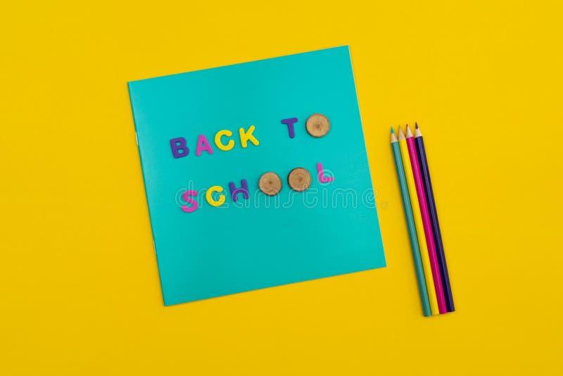 Πίσω στο σχολικό κείμενο σε ένα σημειωματάριο με τα χρωματισμένα μολύβια δίπλα σε το στο πορτοκαλί κίτρινο υπόβαθρο στοκ εικόνες