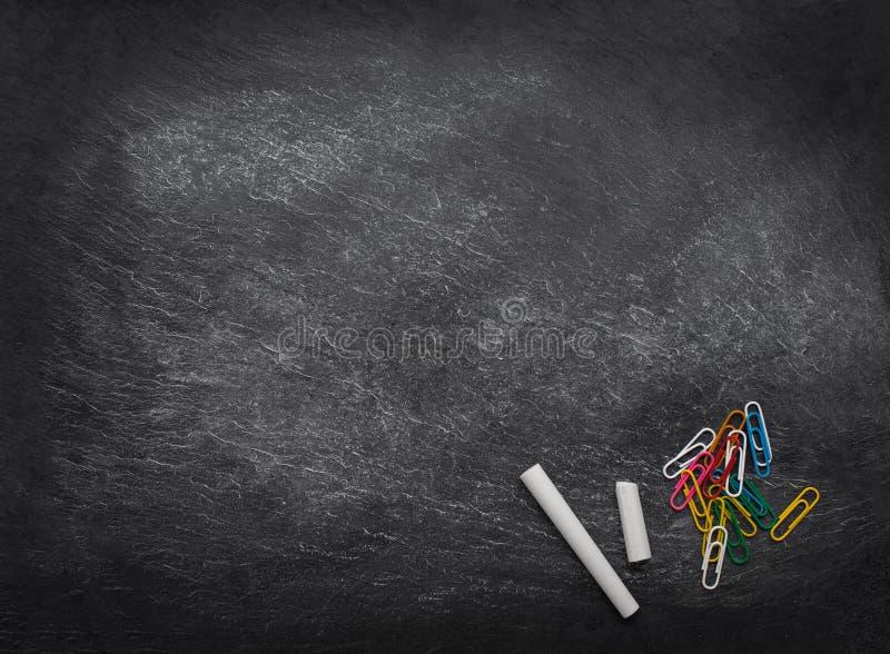 Πίσω στο σχολικό υπόβαθρο Μαύρος πίνακας κιμωλίας με τα κομμάτια κιμωλίας και τους συνδετήρες εγγράφου r r r στοκ εικόνες με δικαίωμα ελεύθερης χρήσης
