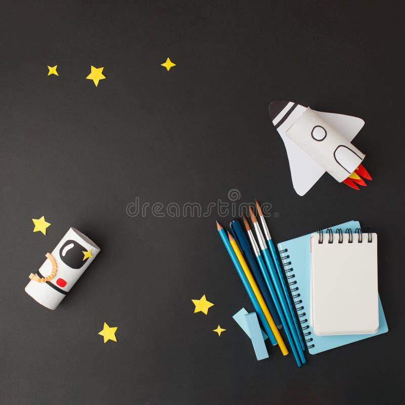 Πίσω στο σχολικό φόντο με ρουκέτα και αστροναύτη από ρολό τουαλέτας σε μαύρο φόντο, χειροτεχνία, δημιουργική ιδέα καλή στοκ φωτογραφίες