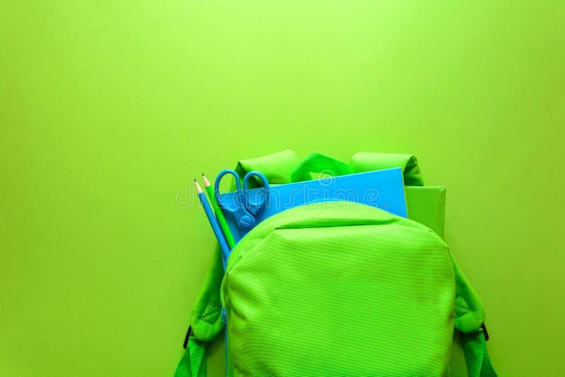 πίσω σχολείο έννοιας Πράσινο σακίδιο πλάτης με τις σχολικές προμήθειες στο πράσινο υπόβαθρο Τοπ όψη στοκ εικόνα