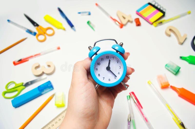 πίσω σχολείο μπλε ξυπνητήρι στο σχολικό γραφείο στα χέρια ενός σπουδαστή χαρτικά εξαρτημάτων Άσπρη ανασκόπηση stickers στοκ εικόνα με δικαίωμα ελεύθερης χρήσης