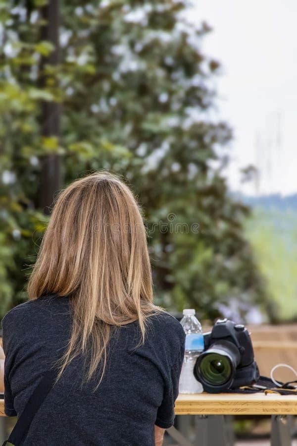 Πίσω της γυναίκας με την όμορφη μακροχρόνια ραβδωμένη συνεδρίαση τρίχας στον εξωτερικό πίνακα πικ-νίκ με τη κάμερα και του μπουκα στοκ εικόνες με δικαίωμα ελεύθερης χρήσης