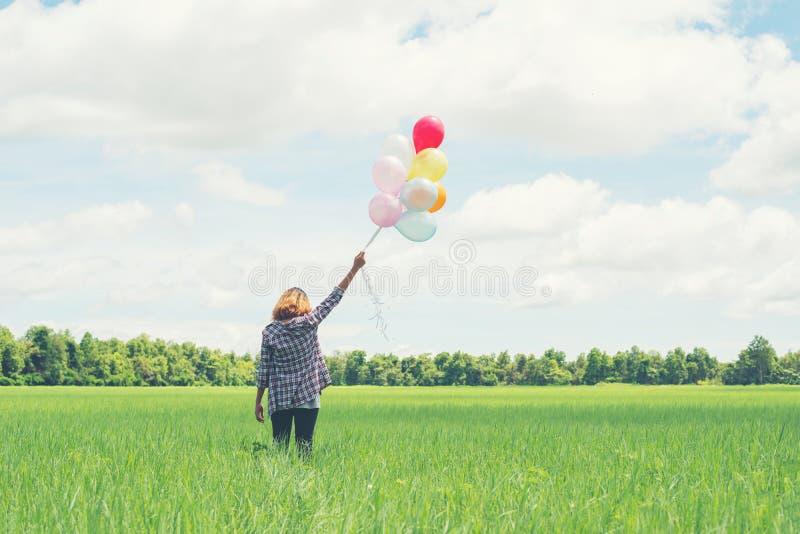Πίσω της νέας ασιατικής γυναίκας hipster με τα χρωματισμένα μπαλόνια στη χλόη στοκ εικόνες με δικαίωμα ελεύθερης χρήσης