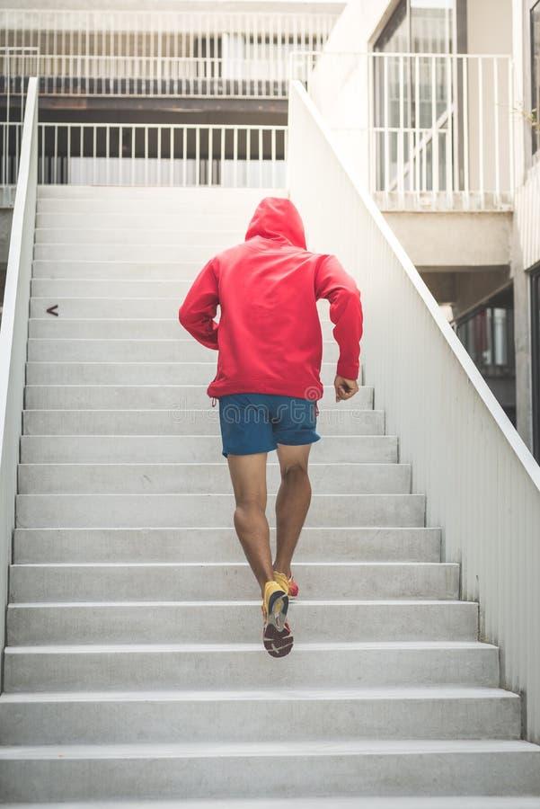Πίσω του αθλητή κόκκινο να δημιουργήσει κουκουλών στα βήματα, θαμπάδα κινήσεων στοκ εικόνες