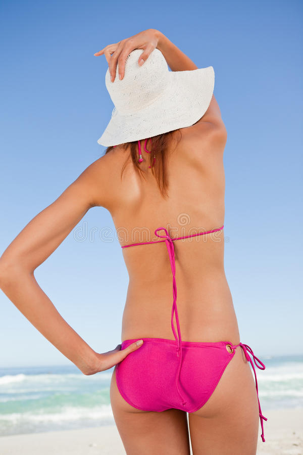 Πίσω όψη ενός ελκυστικού εφήβου στη beachwear εκμετάλλευση το καπέλο αχύρου της στοκ εικόνα με δικαίωμα ελεύθερης χρήσης