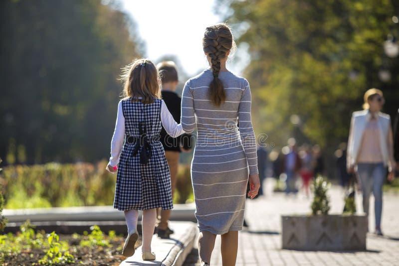 Πίσω όψη παιδιού κοριτσιού και μητέρας με φορέματα μαζί κρατώντας χέρι στοκ εικόνα