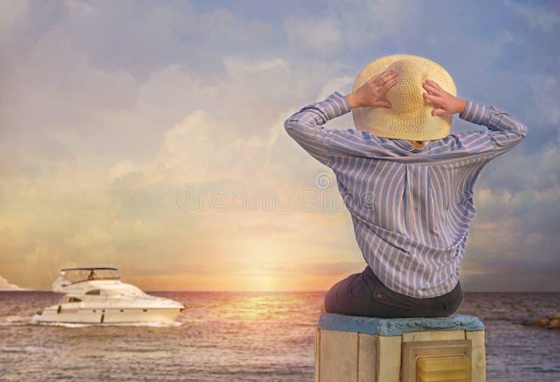 Πίσω όψη της ευτυχισμένης νεαρής γυναίκας που κάθεται σε πέτρες παραλίας στο ηλιοβασίλεμα στοκ εικόνες