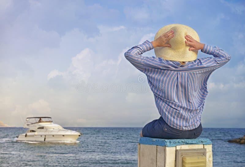 Πίσω όψη της ευτυχισμένης νεαρής γυναίκας που κάθεται σε πέτρες παραλίας στο ηλιοβασίλεμα στοκ εικόνες με δικαίωμα ελεύθερης χρήσης