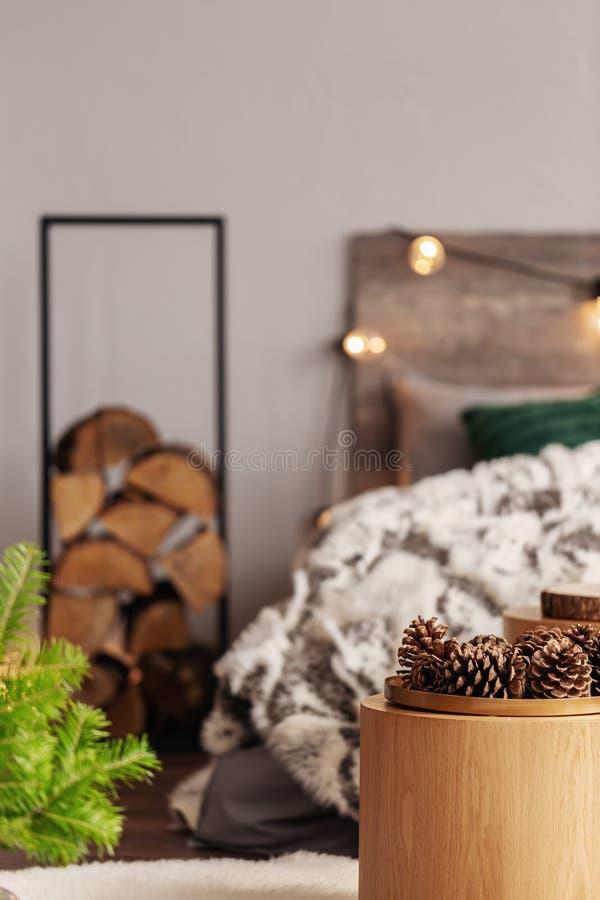 Πίτα από ξύλο σε μεταλλική βάση δίπλα στο κρεβάτι του βασιλιά με ξύλινη επιφάνεια στοκ φωτογραφία με δικαίωμα ελεύθερης χρήσης