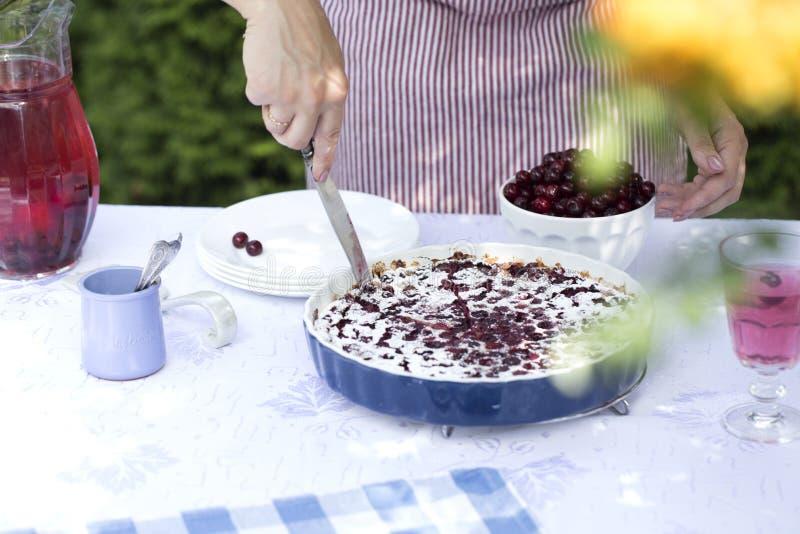 Πίτα κερασιών Clafoutis Τα χέρια γυναικών ` s κόβουν ένα σπιτικό κέικ στοκ εικόνα με δικαίωμα ελεύθερης χρήσης