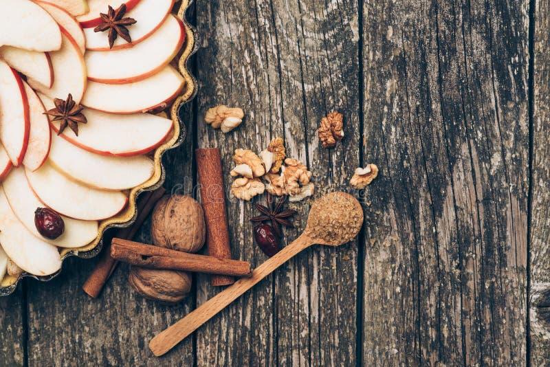Πίτα της Apple ξινή στο αγροτικό ξύλινο υπόβαθρο Συστατικά - μήλα και κανέλα στοκ εικόνα με δικαίωμα ελεύθερης χρήσης