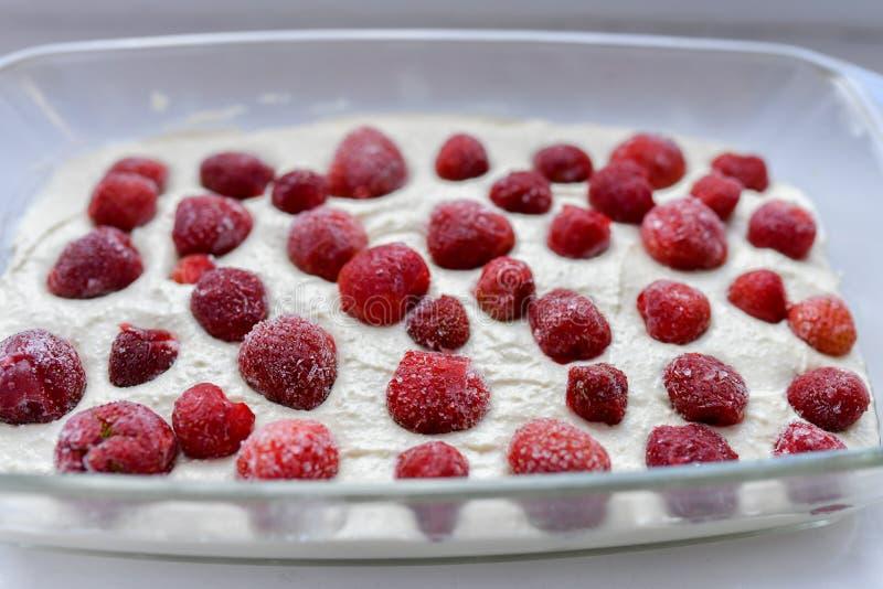 Πίτα φραουλών πριν από το ψήσιμο Ανοικτό κέικ με τις φράουλες πριν από το ψήσιμο Τοποθετημένος σε μια κεραμική μορφή σε ένα μπλε  στοκ εικόνες