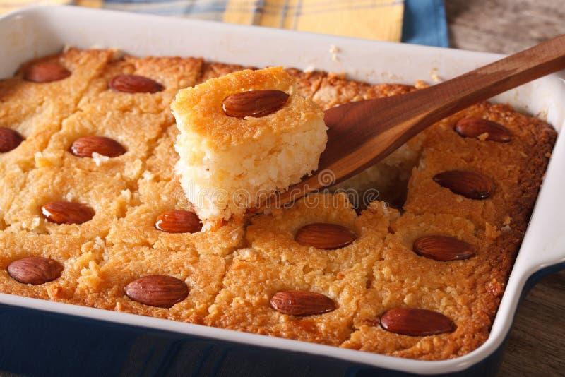 Πίτα Basbousa με τη μακροεντολή αμυγδάλων σε ένα πιάτο ψησίματος οριζόντιος στοκ εικόνες με δικαίωμα ελεύθερης χρήσης