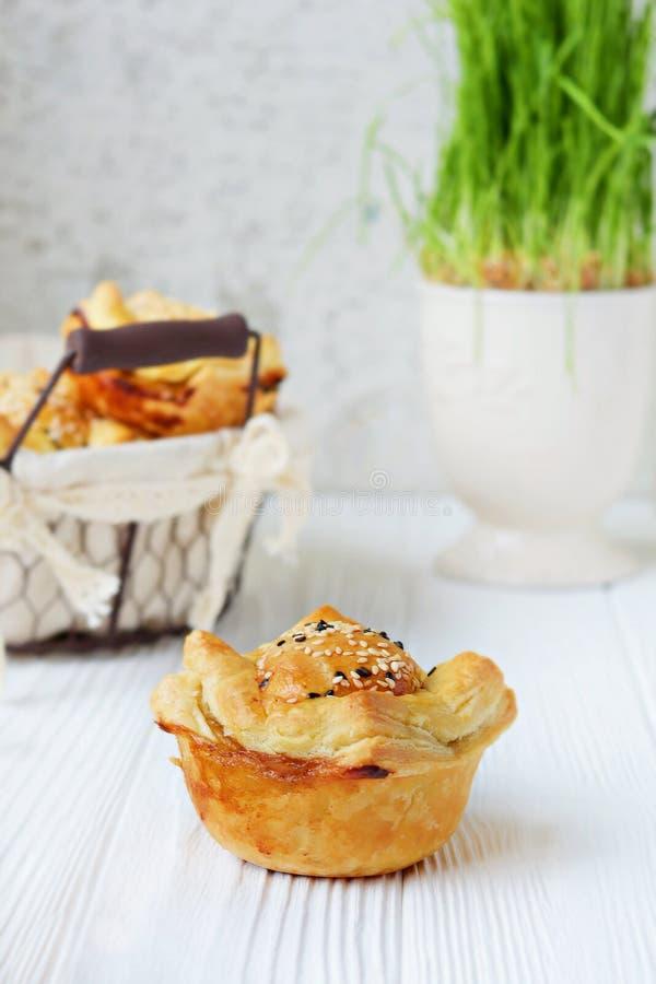 Πίτες κρέατος από τη ζύμη ριπών με τους σπόρους σουσαμιού σε ένα ελαφρύ υπόβαθρο Φρέσκια παραδοσιακή αυστραλιανή πίτα κρέατος στοκ εικόνες