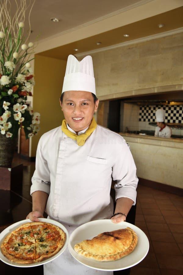 Πίτσα εκμετάλλευσης αρχιμαγείρων στο εστιατόριο στοκ εικόνες με δικαίωμα ελεύθερης χρήσης