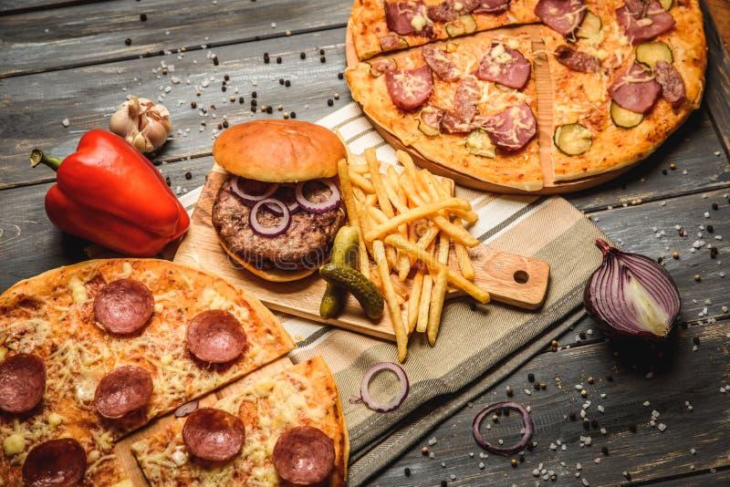 Πίτσα και χάμπουργκερ στο ξύλινο υπόβαθρο στοκ εικόνα με δικαίωμα ελεύθερης χρήσης