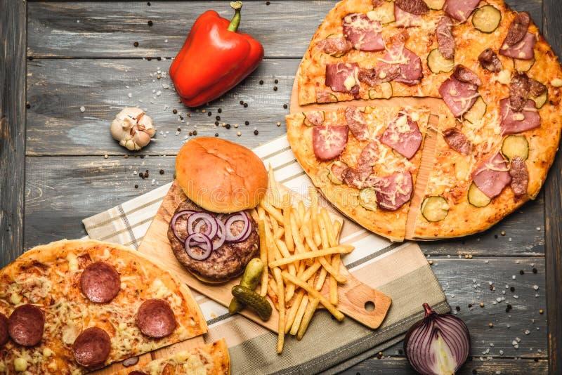Πίτσα και χάμπουργκερ στο ξύλινο υπόβαθρο στοκ εικόνες
