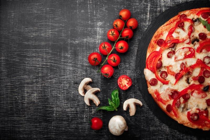 Πίτσα με τα καπνισμένα λουκάνικα, το τυρί, τα μανιτάρια, τις ντομάτες κερασιών, τα πιπέρια κουδουνιών και τα πράσινα σε μια πέτρα στοκ εικόνες