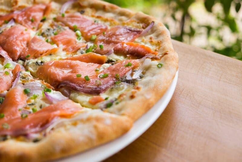 Πίτσα με τον καπνισμένο σολομό στοκ εικόνα
