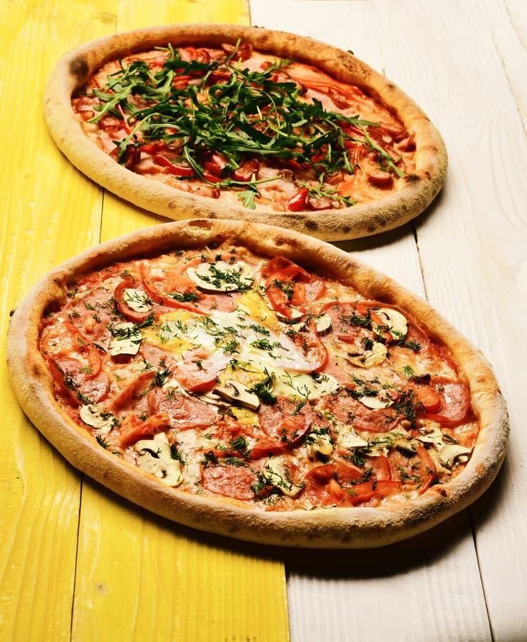 Πίτσα με pepperoni, τα μανιτάρια και το αυγό στο κίτρινο ξύλινο υπόβαθρο στοκ εικόνες