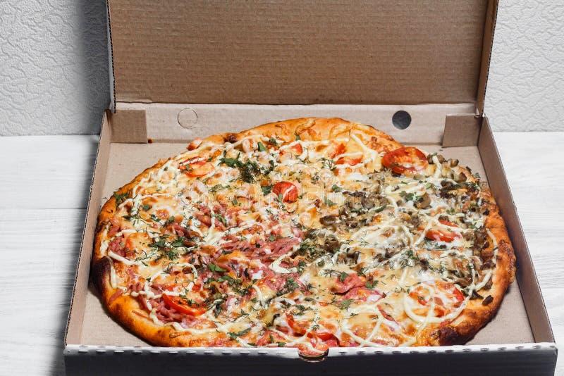Πίτσα σε ένα κουτί από χαρτόνι σε ένα άσπρο ξύλινο υπόβαθρο επάνω από την όψη Παράδοση πιτσών Επιλογές πιτσών στοκ εικόνες