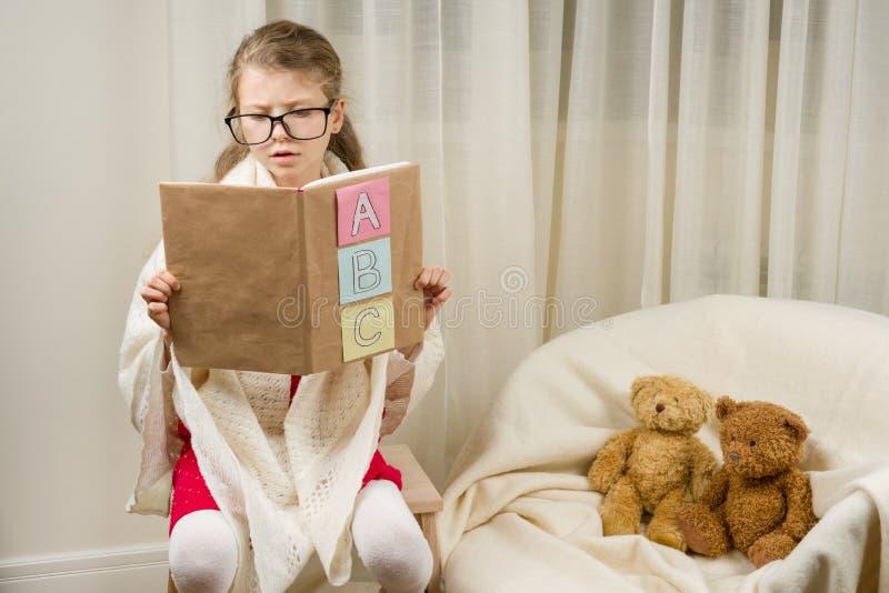 Παίζοντας δάσκαλος σχολείου παιδιών με τις teddy αρκούδες στο σπίτι στοκ φωτογραφίες