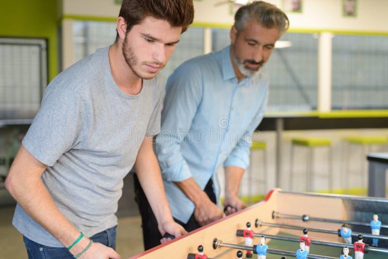 Παίζοντας επιτραπέζιο ποδόσφαιρο πατέρων και γιων στοκ φωτογραφίες