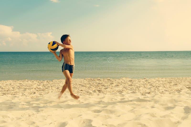 Παίζοντας και τρέχοντας σφαίρα αγοριών του valleyball στην παραλία θάλασσας στοκ εικόνες