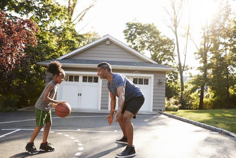 Παίζοντας καλαθοσφαίριση πατέρων και γιων Driveway στο σπίτι στοκ φωτογραφίες