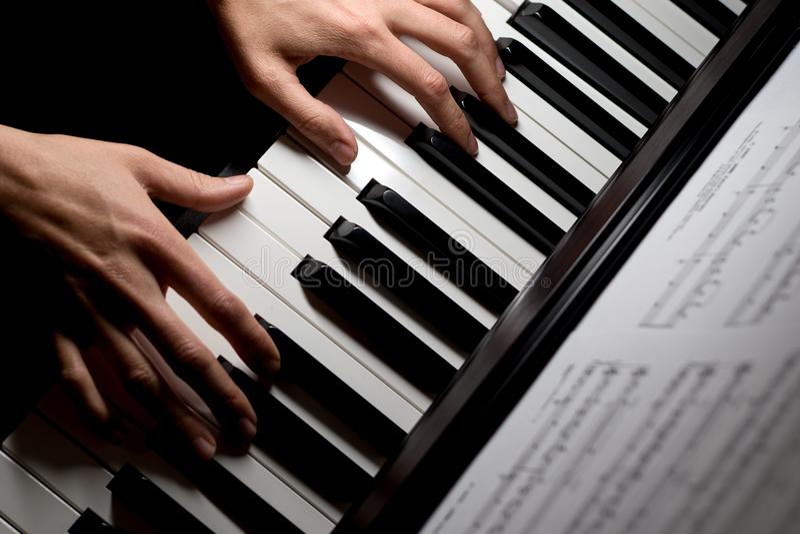 Παίζοντας μουσική πιάνων Pianist στο ηλεκτρικό πληκτρολόγιο, στο μαύρο υπόβαθρο στοκ εικόνα με δικαίωμα ελεύθερης χρήσης