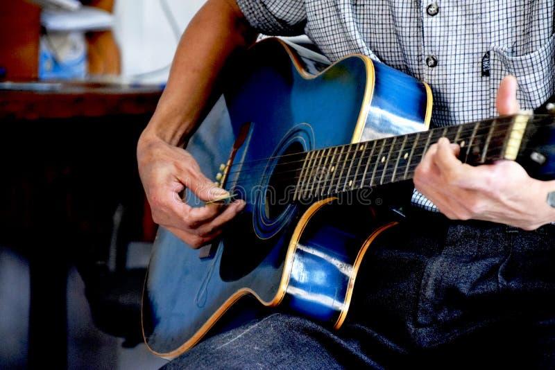 Παίζοντας μουσική στην μπλε κιθάρα στοκ φωτογραφία