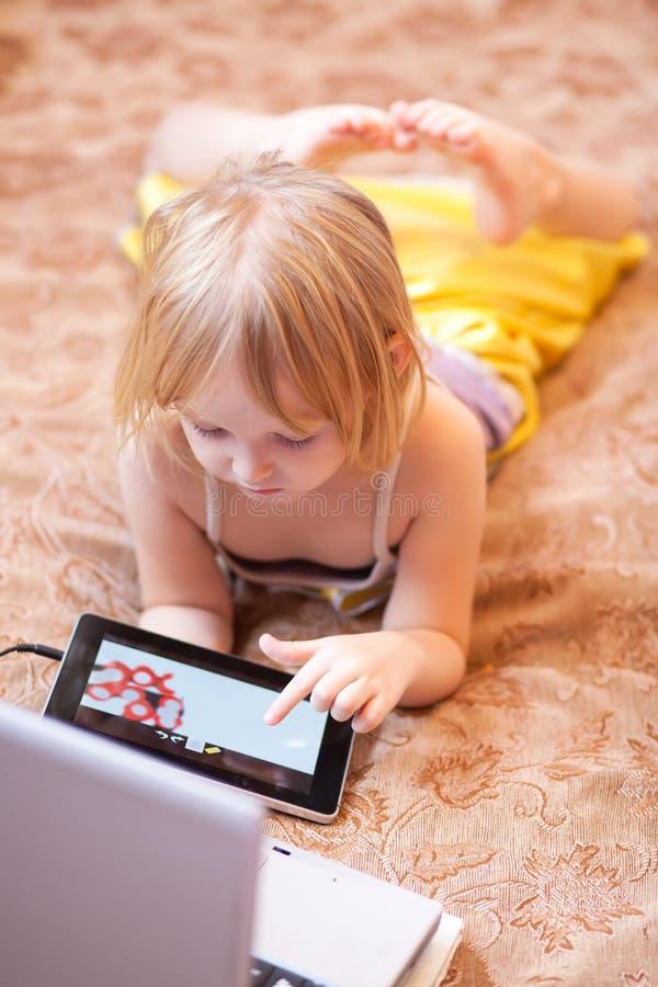 Παίζοντας παιχνίδι στον υπολογιστή μικρών κοριτσιών που χρησιμοποιεί την ταμπλέτα στο εσωτερικό στοκ φωτογραφίες με δικαίωμα ελεύθερης χρήσης