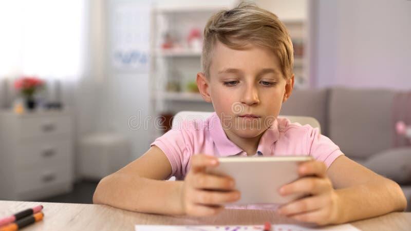 Παίζοντας παιχνίδι smartphone σχολικών αγοριών που σύρει αντ' αυτού, εθισμός συσκευών, χόμπι στοκ εικόνα