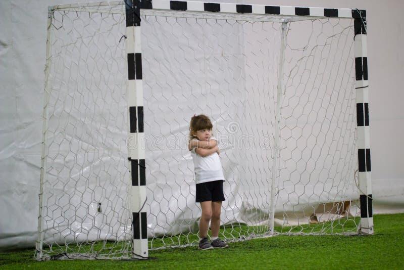 Παίζοντας ποδόσφαιρο στο εσωτερικό Ένα μικρό κορίτσι που στέκεται στις πύλες ποδοσφαίρου και που αγκαλιάζεται στοκ εικόνες