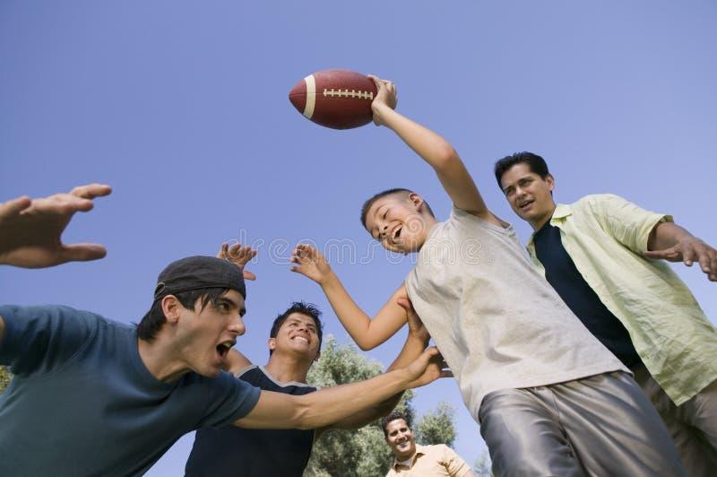 Παίζοντας ποδόσφαιρο αγοριών (13-15) με την ομάδα χαμηλής άποψης γωνίας νεαρών άνδρων. στοκ εικόνα με δικαίωμα ελεύθερης χρήσης
