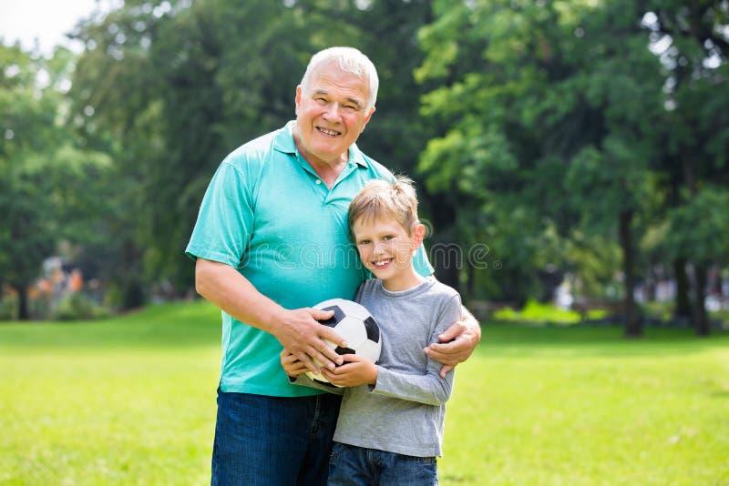 Παίζοντας ποδόσφαιρο εγγονών και παππούδων στοκ εικόνες