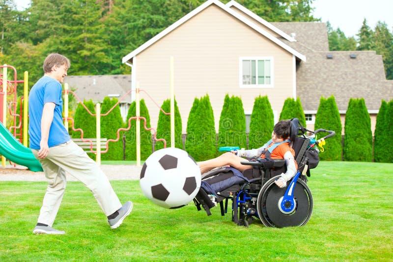 Παίζοντας ποδόσφαιρο πατέρων με το με ειδικές ανάγκες γιο στο wheelchai στοκ εικόνες