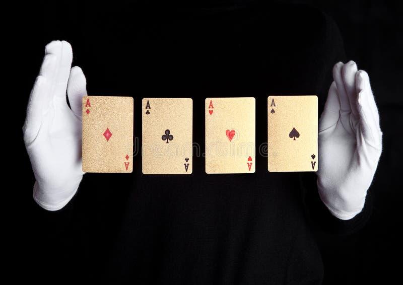 Παίζοντας τέχνασμα καρτών με τα χέρια άσσων με τα γάντια στοκ εικόνες