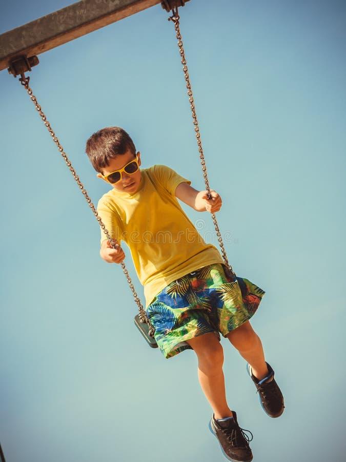 Παίζοντας ταλάντευση αγοριών από το ταλάντευση-σύνολο στοκ φωτογραφία με δικαίωμα ελεύθερης χρήσης