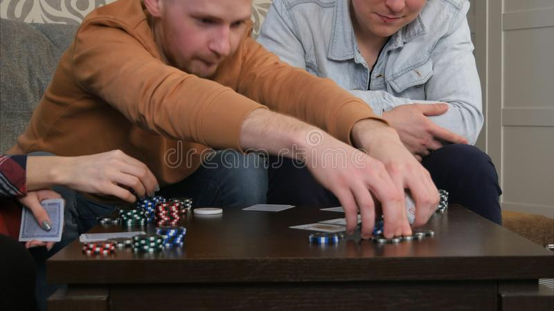 Παίκτες πόκερ εφήβων που στοιχηματίζουν τα τσιπ στο παιχνίδι πόκερ στοκ φωτογραφία