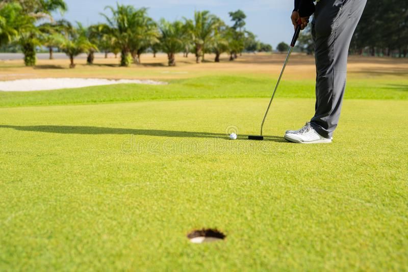 Παίκτης γκολφ που βάζει τη σφαίρα γκολφ στο πράσινο γκολφ, φλόγα φακών στον καθορισμένο χρόνο βραδιού ήλιων στοκ εικόνες