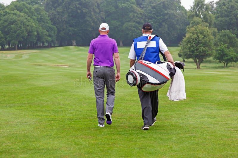 Παίκτης γκολφ και caddy περπατώντας επάνω μια στενή δίοδο στοκ φωτογραφίες