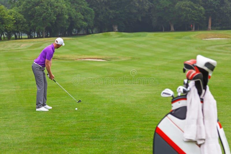 Παίκτης γκολφ που εξετάζει τη σφαίρα σε μια ισοτιμία 4 στενή δίοδος. στοκ εικόνες με δικαίωμα ελεύθερης χρήσης