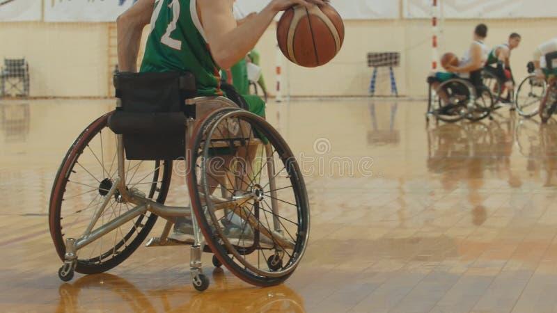 Παίχτης μπάσκετ αναπηρικών καρεκλών που στάζει τη σφαίρα γρήγορα κατά τη διάρκεια της κατάρτισης των με ειδικές ανάγκες αθλητικών στοκ εικόνα