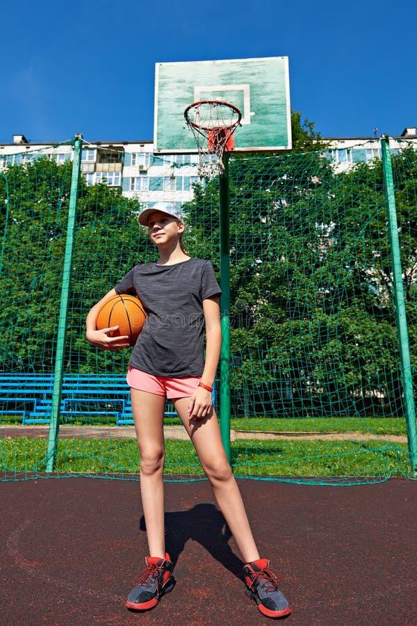 Παίχτης μπάσκετ κοριτσιών με τη σφαίρα στην παιδική χαρά στοκ εικόνες με δικαίωμα ελεύθερης χρήσης