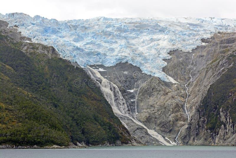 Παγετώνας και καταρράκτης στα μακρινά βουνά στοκ φωτογραφίες