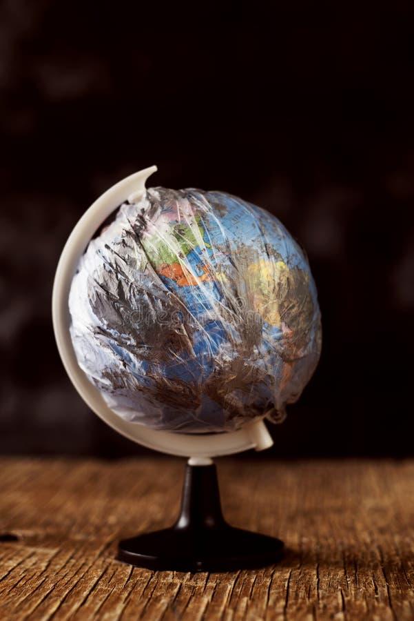 Παγκόσμια σφαίρα που τυλίγεται σε ένα βρώμικο πλαστικό στοκ φωτογραφία με δικαίωμα ελεύθερης χρήσης
