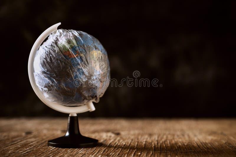 Παγκόσμια σφαίρα που τυλίγεται σε ένα βρώμικο πλαστικό στοκ εικόνες