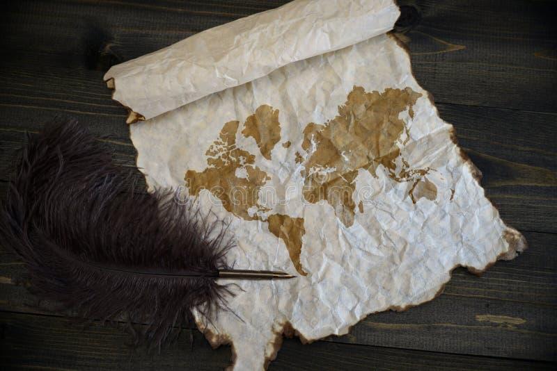 Παγκόσμιος χάρτης σε εκλεκτής ποιότητας χαρτί με την παλαιά μάνδρα στο ξύλινο γραφείο σύστασης στοκ φωτογραφία με δικαίωμα ελεύθερης χρήσης