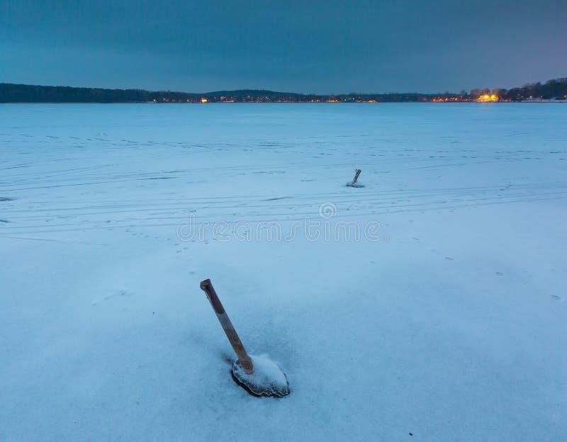 Παγωμένη λίμνη με την παλαιά πρόσδεση για τις βάρκες στοκ εικόνα